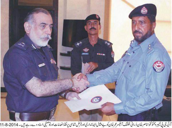 IG KP Nasir Khan Durrani is shaking hand with an officer who returned a 6.5 million rupees bag.jpg