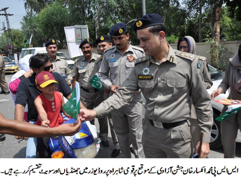 SSP Inkisar Ahmad Khan distributing flags and sweets among road users.JPG